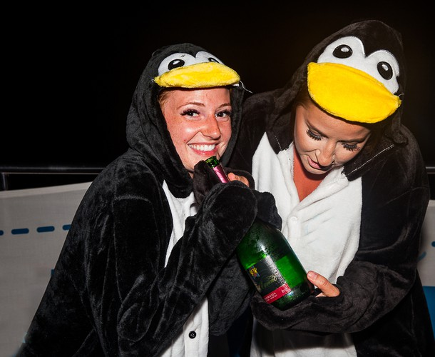 Two women wearing penguin costumes hold a large bottle of champagne.
