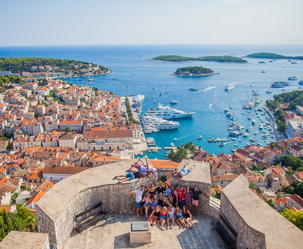 A group of travelers pose at a lookout point over the town of Hvar, Croatia.